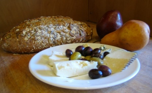 still life with 5-grain loaf, cheese & olives